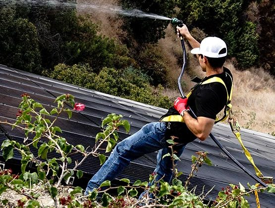 Man Cleaning Solar Panels with Jet Pump